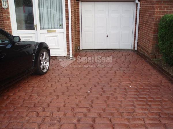 Red imprinted concrete driveway after sealing